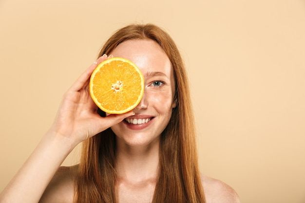 Mujer hermosa joven pelirroja sosteniendo naranja