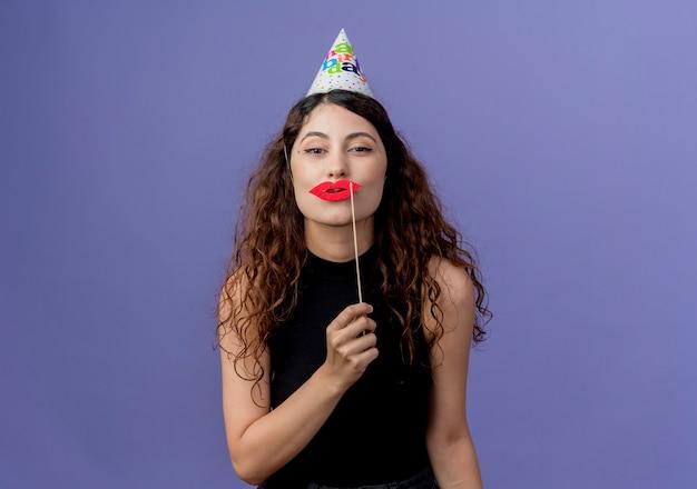 Mujer hermosa joven con el pelo rizado en gorro de fiesta sosteniendo palos de fiesta de pie sobre la pared azul