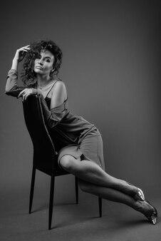 Mujer hermosa joven con el pelo rizado posando en blanco y negro