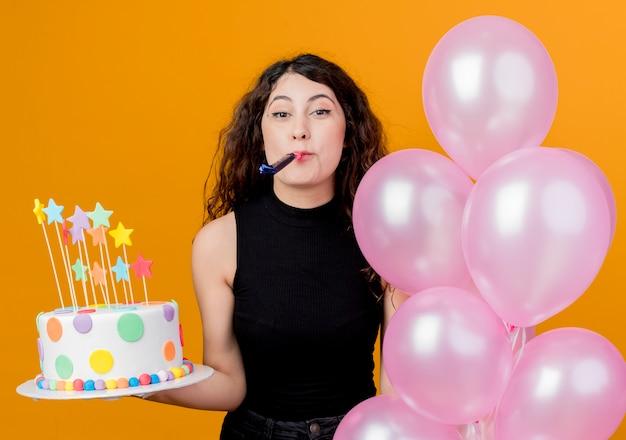 Mujer hermosa joven con el pelo rizado que sostiene la torta de cumpleaños y un montón de globos de aire que soplan el concepto de fiesta de cumpleaños feliz y emocionado del silbido que se coloca sobre la pared naranja