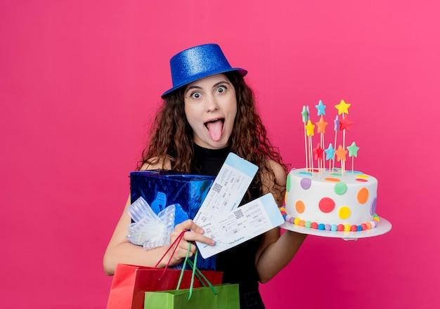Mujer hermosa joven con el pelo rizado en un sombrero de fiesta con caja de regalo de pastel de cumpleaños y boletos de avión concepto de fiesta de cumpleaños feliz loco sobre rosa