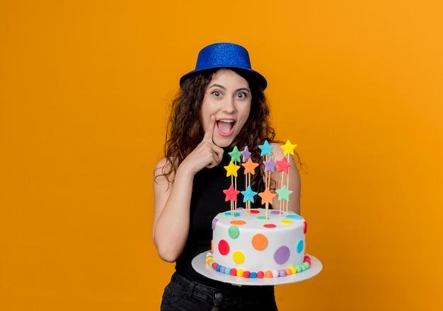 Mujer hermosa joven con el pelo rizado en un sombrero de fiesta sosteniendo la torta de cumpleaños alegre y alegre de pie sobre la pared naranja