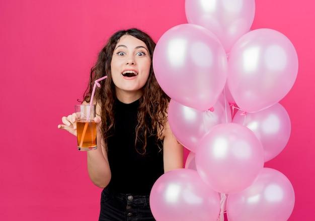 Mujer hermosa joven con el pelo rizado sosteniendo un montón de globos de aire y un cóctel mirando sorprendido sonriendo alegremente de pie sobre la pared rosa