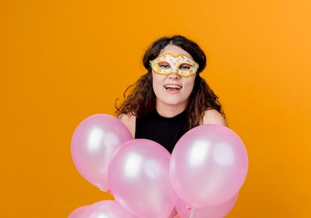 Mujer hermosa joven con el pelo rizado sosteniendo un montón de globos de aire en la máscara de fiesta concepto de fiesta de cumpleaños feliz y alegre sobre naranja