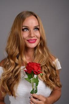 Mujer hermosa joven con el pelo rubio contra el fondo gris