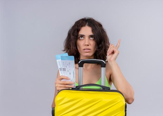 Mujer hermosa joven pensativa del viajero que sostiene los billetes de avión y la maleta y que señala hacia arriba en la pared blanca aislada con el espacio de la copia