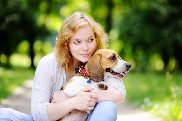 Mujer hermosa joven con el perro del beagle en el parque del verano. amante mujer dueña con su mascota doméstica.