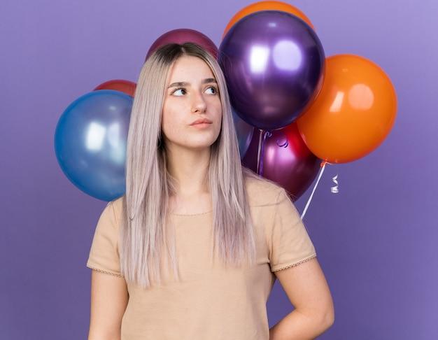 Mujer hermosa joven de pie delante de globos aislados en la pared azul