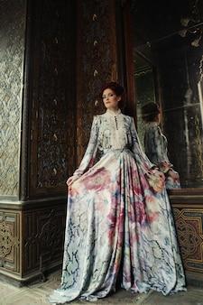 Mujer hermosa joven de pie en la sala del palacio con espejo.