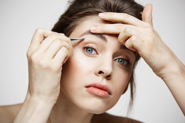 La mujer hermosa joven con la piel limpia perfecta depila las cejas. tratamiento facial.