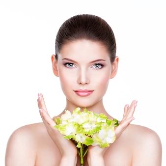 Mujer hermosa joven con una piel limpia y sana con flor en sus manos -
