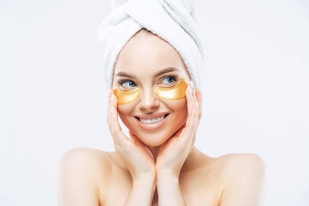 Mujer hermosa joven con piel sana y fresca, aplica parches dorados debajo de los ojos contra las ojeras