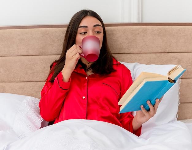 Mujer hermosa joven en pijama rojo relajante en la cama