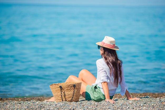Mujer hermosa joven en la playa tomando el sol