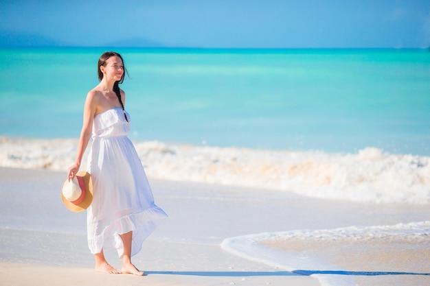 Mujer hermosa joven en la playa tropical de arena blanca. niña caucásica con fondo de sombrero del mar