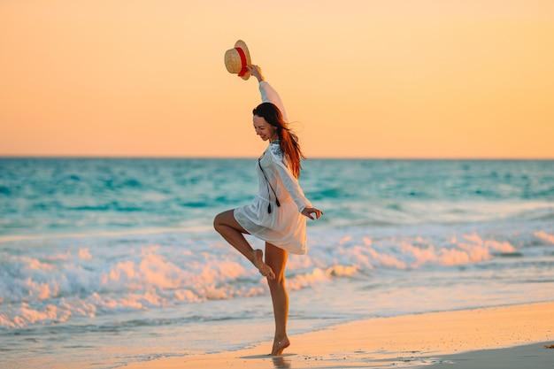 Mujer hermosa joven en la playa tropical en puesta de sol.