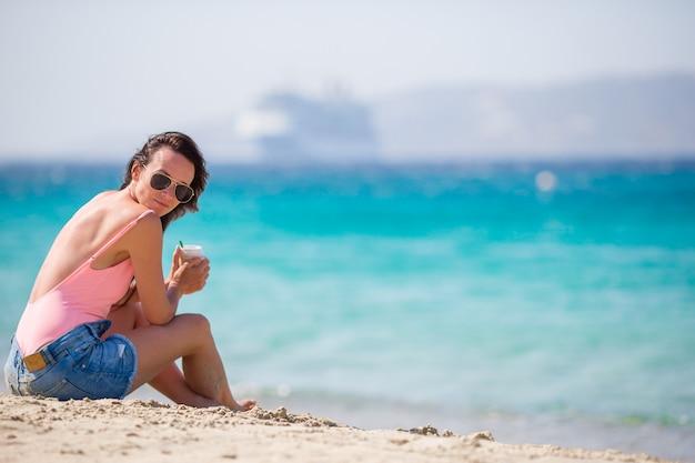 Mujer hermosa joven en la playa durante vacaciones tropicales. chica disfruta su wekeend en una de las hermosas playas de mykonos, grecia, europa.