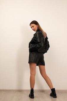 Mujer hermosa joven posando en estudio en pantalones cortos de cuero negro, botas y chaqueta