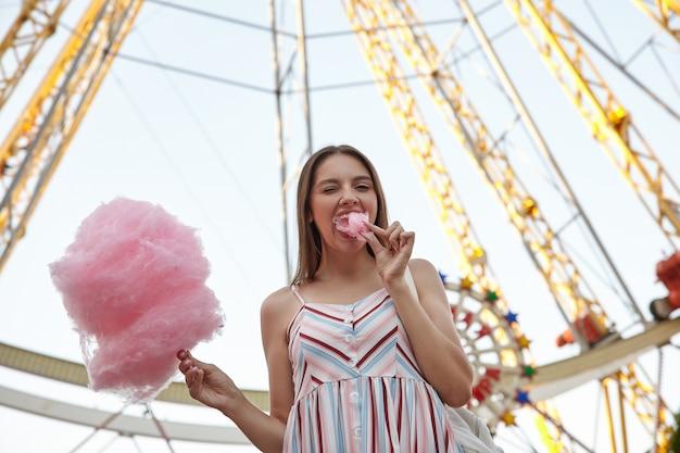 Mujer hermosa joven positiva en vestido de verano de pie sobre la noria en el parque de atracciones en un día cálido, sosteniendo algodón de azúcar en un palo y poniendo un pedazo en la boca, guiñando un ojo