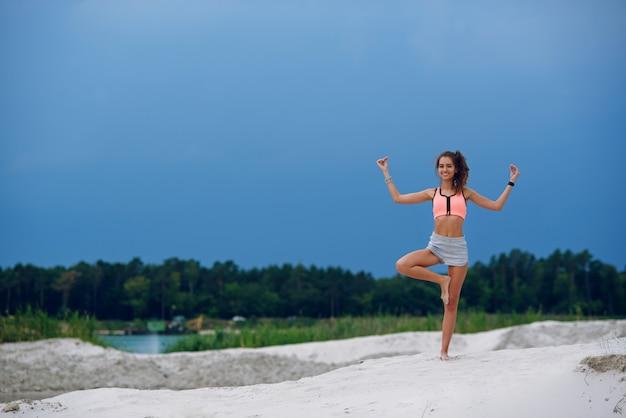 Mujer hermosa joven practicando yoga pose de árbol al aire libre en la playa