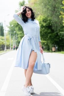 Mujer hermosa joven en la presentación azul del vestido