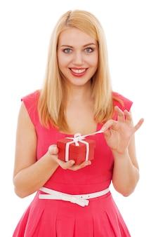 Mujer hermosa joven que abre una caja de regalo