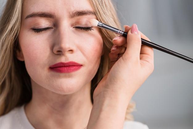 Mujer hermosa joven que aplica maquillaje por el cepillo