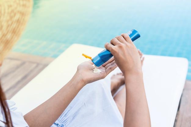 Mujer hermosa joven que aplica el protector solar o la loción del bronceador en su cuerpo para la protección solar de la piel en la piscina, concepto de las vacaciones de verano.
