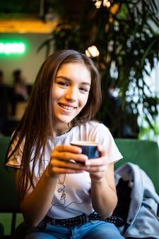 Mujer hermosa joven que bebe capucino en café