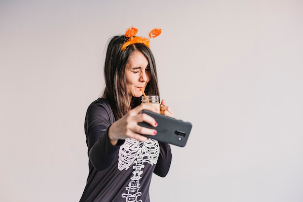 Mujer hermosa joven que bebe el zumo de naranja y que toma un selfie con el teléfono móvil. usando un disfraz de esqueleto blanco y negro. concepto de halloween adentro