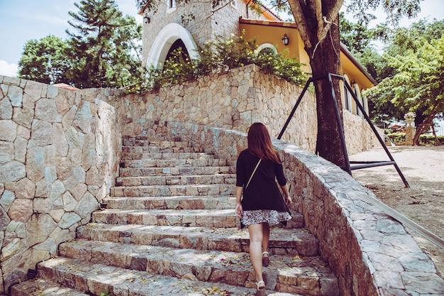 Mujer hermosa joven que camina encima de las escaleras de piedra con el fondo natural. paso para el concepto de éxito.