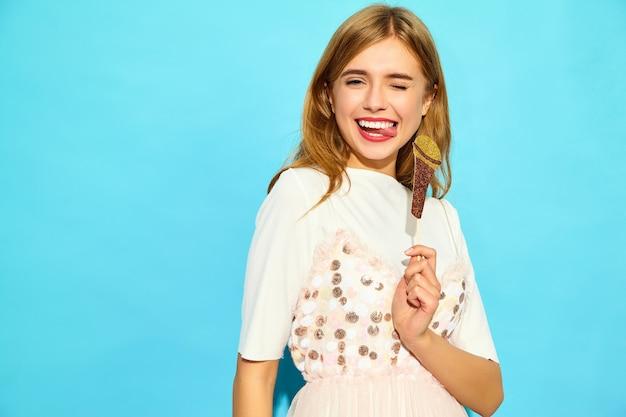 Mujer hermosa joven que canta con el micrófono falso de los apoyos. moda mujer en ropa casual de verano. modelo divertido aislado en la pared azul