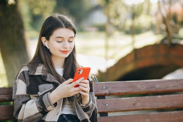 Mujer hermosa joven que se coloca en un banco usando la computadora portátil