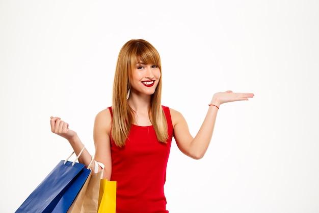 Mujer hermosa joven que se coloca con las compras sobre la pared blanca