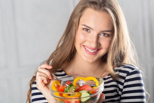 Mujer hermosa joven que come la comida sana - ensalada