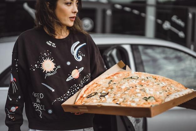 Mujer hermosa joven que come una rebanada de pizza en la calle de la ciudad