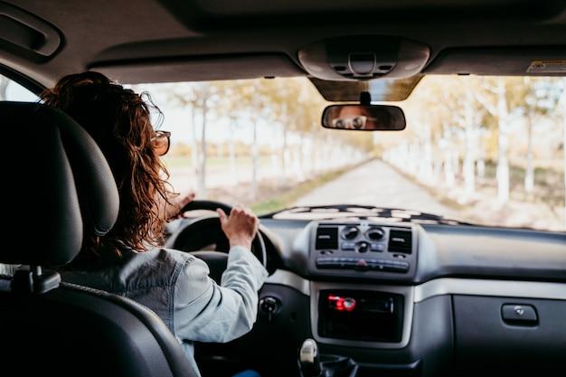 Mujer hermosa joven que conduce una furgoneta por un camino de árboles. concepto de viaje, vista desde el interior