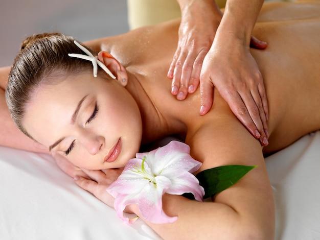 Mujer hermosa joven que consigue relajante masaje de hombros en salón de belleza - interior