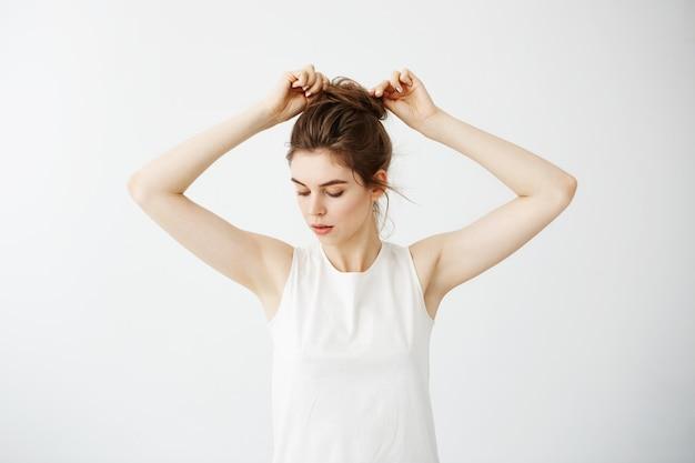 Mujer hermosa joven que corrige el bollo del pelo.