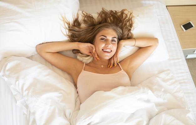 Mujer hermosa joven que se despierta en su cama completamente descansado. mujer que se extiende en la cama después de despertarse.