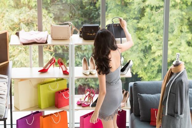Mujer hermosa joven que disfruta en compras en la tienda. señora eligiendo zapatos, bolsos y accesorios.