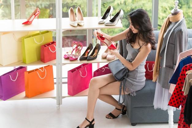 Mujer hermosa joven que disfruta en compras en la tienda.