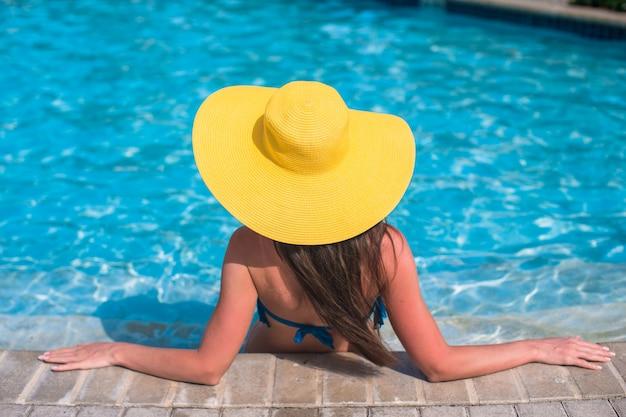 Mujer hermosa joven que disfruta de vacaciones en la piscina
