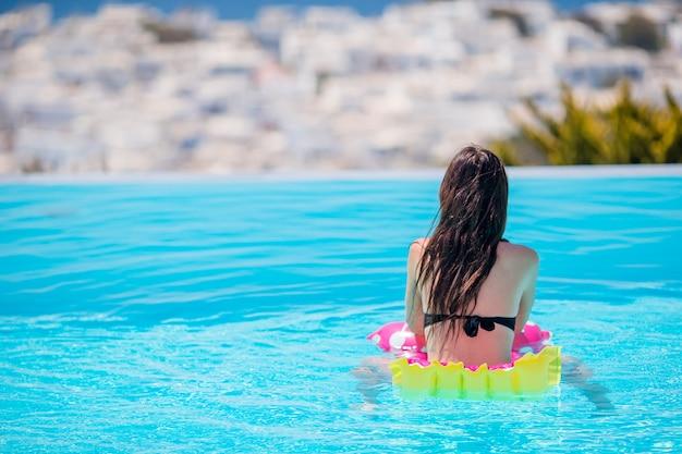 Mujer hermosa joven que disfruta de vacaciones de verano en piscina al aire libre