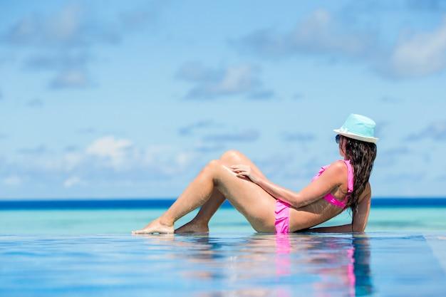 Mujer hermosa joven que disfruta de vacaciones de verano en piscina de lujo