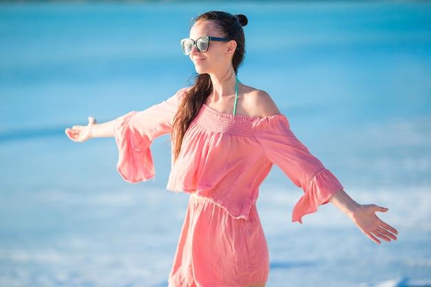 Mujer hermosa joven que se divierte en la costa tropical.