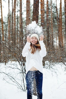 Mujer hermosa joven que se divierte en el parque de invierno. vacaciones de navidad, concepto de vacaciones de invierno.