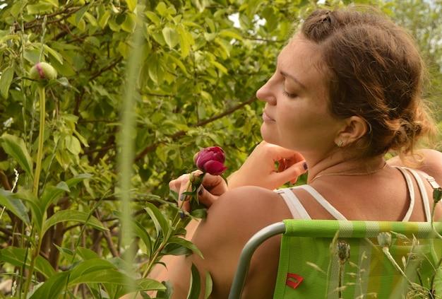 Mujer hermosa joven que se divierte que huele las flores que se sientan en una silla en el jardín en un día de verano