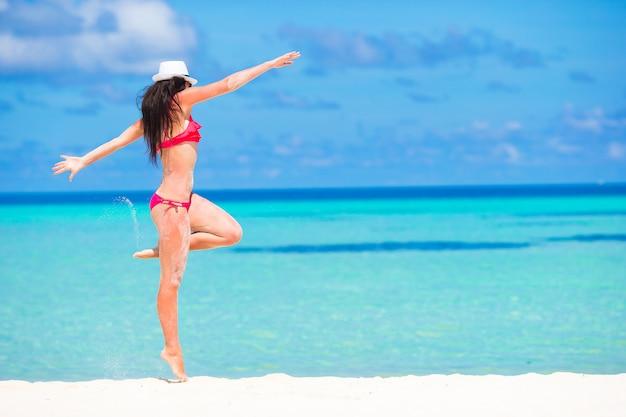 Mujer hermosa joven que se divierte durante vacaciones de la playa