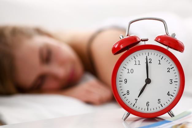 Mujer hermosa joven que duerme bien en el concepto de alarma de la mañana